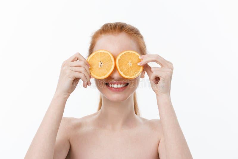 Portret van een vrolijk jong meisje die twee plakken van een sinaasappel houden bij haar gezicht over witte muurachtergrond stock foto