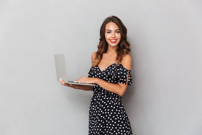 Portret van een vrolijk jong meisje in kleding over grijs stock afbeelding