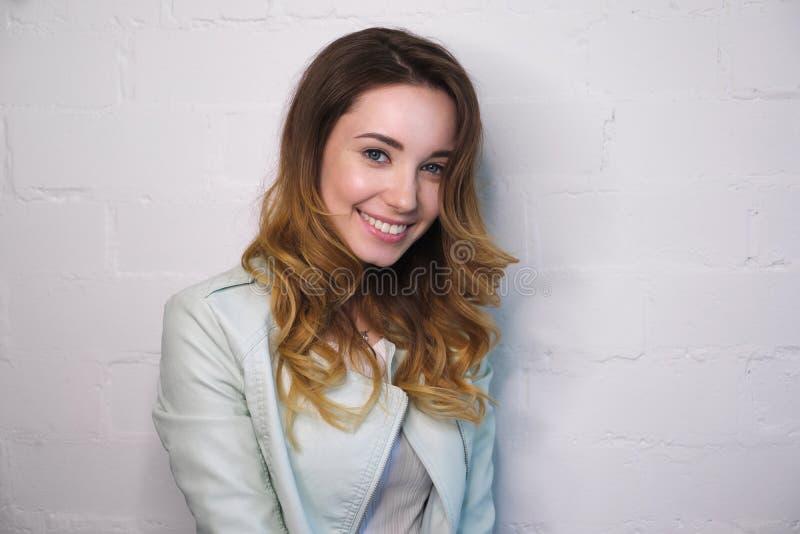 Portret van een vrolijk jong meisje met krullen en een glimlach op een witte achtergrond stock afbeelding