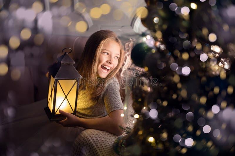Portret van een vrolijk schattig meisje bij een kerstboom met een lantaarn Nieuwjaarsvakantie royalty-vrije stock fotografie