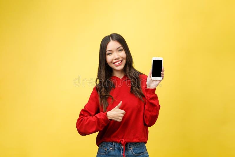 Portret van een vrolijk toevallig meisje die mobiele telefoon houden die en vinger richten weg over gele achtergrond wordt geïsol royalty-vrije stock afbeelding