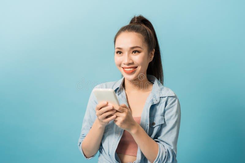 Portret van een vrolijk toevallig meisje die mobiele telefoon over blauwe achtergrond houden stock foto