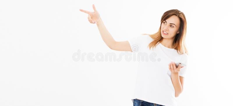 Portret van een vrolijk toevallig mooi meisje die mobiele telefoon houden die en vinger richten weg over witte achtergrond wordt  royalty-vrije stock afbeeldingen