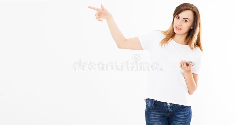 Portret van een vrolijk toevallig mooi meisje die mobiele telefoon houden en vinger weg over witte achtergrond richten royalty-vrije stock foto's