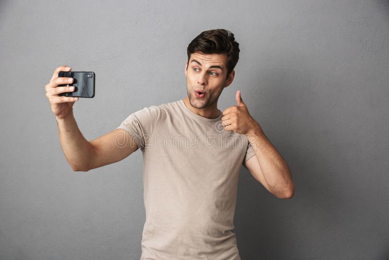 Portret van een vrolijke jonge geïsoleerde mens in t-shirt stock foto's