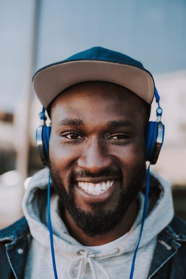 Portret van een vrolijke jonge mens die aan muziek luisteren royalty-vrije stock afbeelding