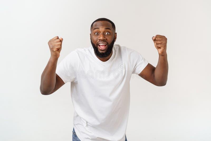 Portret van een vrolijke jonge mens die die met wapens schreeuwen in succes worden opgeheven royalty-vrije stock foto