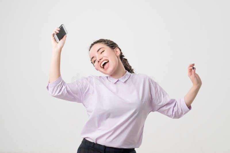 Portret van een vrolijke leuke vrouw het luisteren muziek en geïsoleerd dansen royalty-vrije stock fotografie