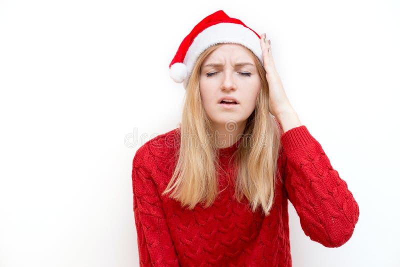 Portret van een vrolijke mooie vrouw, een emotioneel meisje in santa claus kerst dat lijdt aan hoofdpijn, wanhopig en royalty-vrije stock foto's