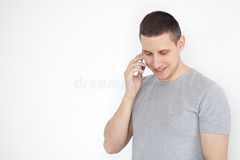 Portret van een vrolijke, positieve, aantrekkelijke kerel met stoppelveld in een grijze T-shirt, die op de telefoon op een grijze royalty-vrije stock foto