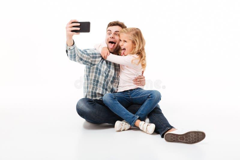 Portret van een vrolijke vader en zijn kleine dochter stock afbeelding