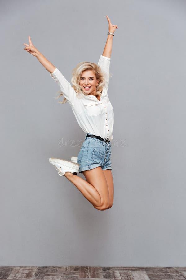 Portret van een vrolijke vrouw die en v-gebaar springen tonen stock fotografie