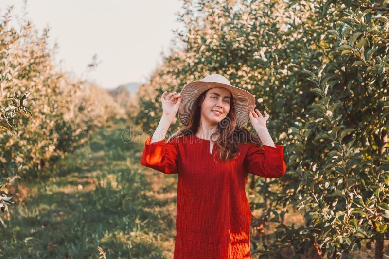 Portret van een vrouw in de tuin Een jonge en mooie vrouw in een rode haar handen houden aan haar hoed en kleding die zoet glimla stock foto