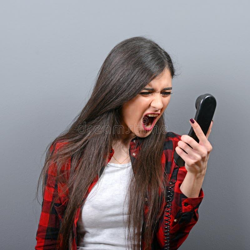 Portret van een vrouw die bij telefoon tegen grijze achtergrond schreeuwt royalty-vrije stock foto