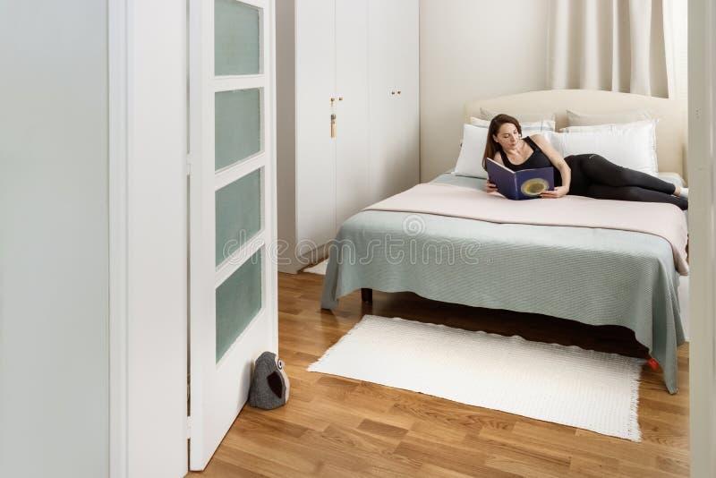 Portret van een vrouw die een boek lezen die op haar bed leggen stock foto's