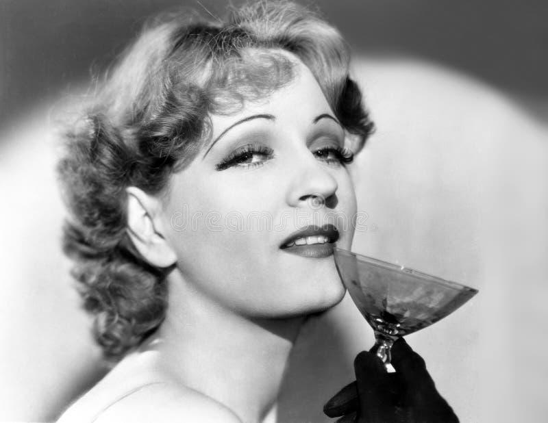 Portret van een vrouw die een martini-glas houden (Alle afgeschilderde personen leven niet langer en geen landgoed bestaat Levera stock foto