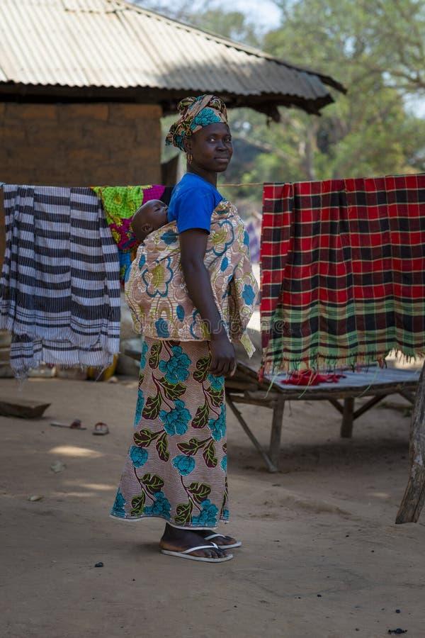 Portret van een vrouw die haar baby op schouders, in het dorp van Mandina Mandinga in Gabu Region vervoeren stock afbeelding
