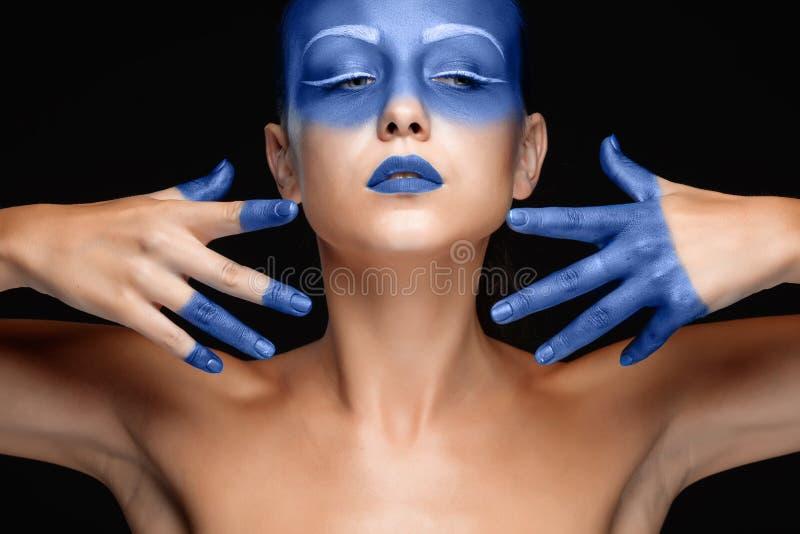 Portret van een vrouw die stellend met blauwe verf behandelt stock afbeelding