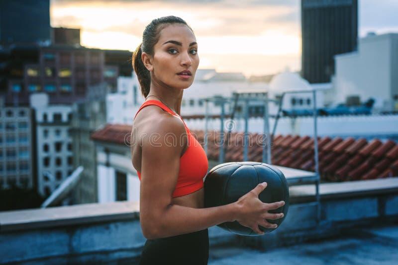Portret van een vrouw die zich op dak bevinden die een geneeskundebal houden stock foto