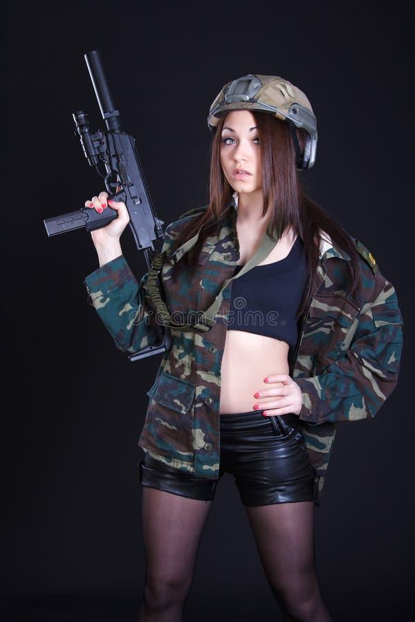 Portret van een vrouw in een militair uniform met een machinepistool stock fotografie