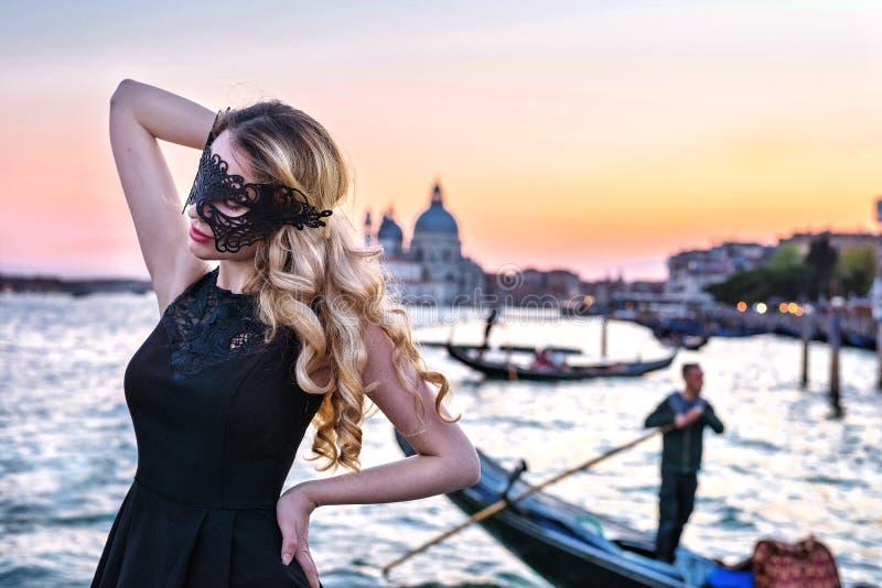 Portret van een vrouw met een geheimzinnige blik op zonsondergang in Venetië Meisje die een zwart masker en een gondel op Grand C royalty-vrije stock afbeelding