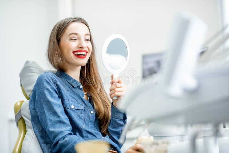 Portret van een vrouw met gezonde glimlach in het tandbureau stock afbeelding