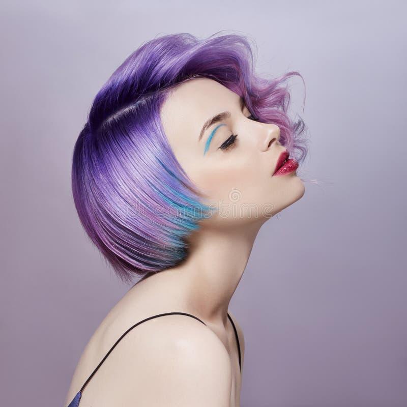 Portret van een vrouw met helder gekleurd vliegend haar, alle schaduwen van purple Haarkleuring, mooie lippenmake-up Haar het fla stock foto's