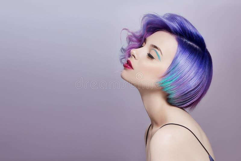 Portret van een vrouw met helder gekleurd vliegend haar, alle schaduwen van purple Haarkleuring, mooie lippenmake-up Haar het fla stock foto