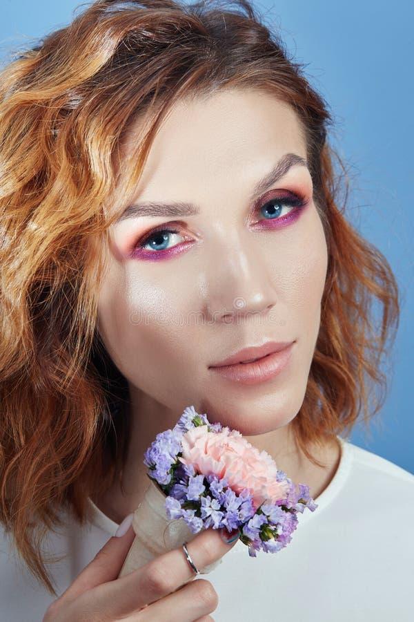 Portret van een vrouw met heldere rode schaduwen op haar ogen en perfecte make-up op haar gezicht Meisjesglimlachen bij de blauwe stock afbeeldingen