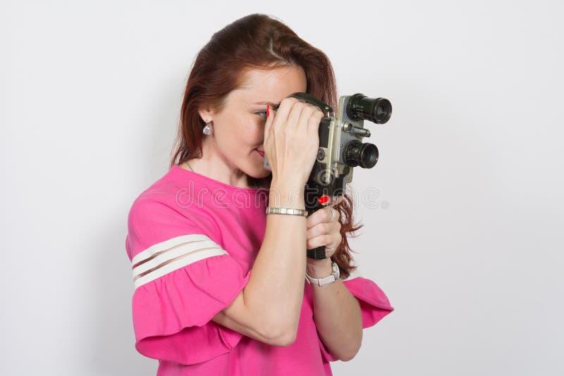 Portret van een vrouw met retro filmcamera op witte achtergrond wordt geïsoleerd die royalty-vrije stock fotografie