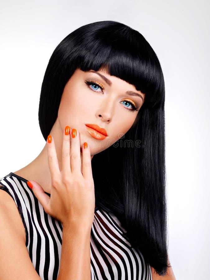 Portret van een vrouw met rode spijkers en glamourmake-up stock foto's