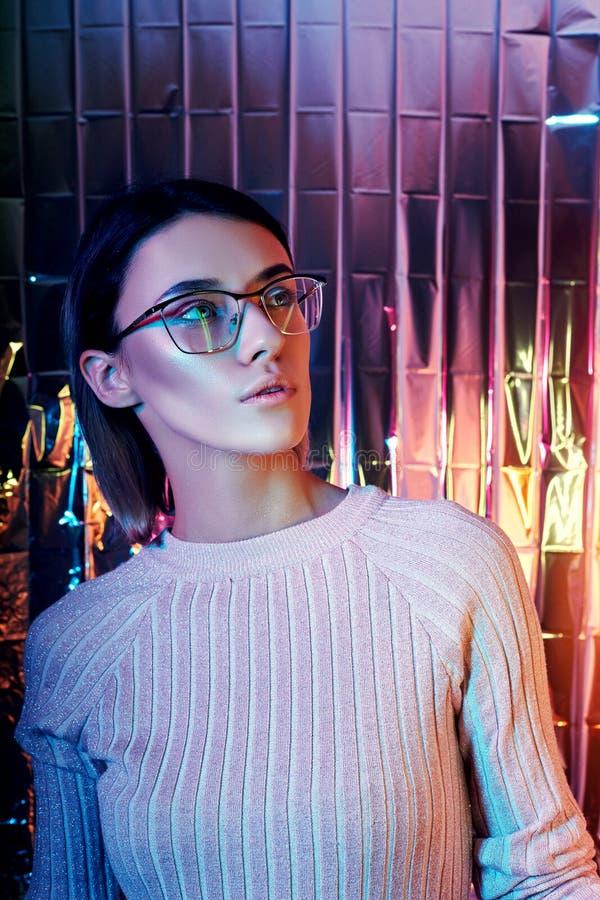 Portret van een vrouw in neon gekleurde bezinningsglazen op de achtergrond Goede visie, perfecte make-up op meisjesgezicht Het Po stock afbeelding