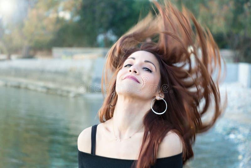 Portret van een vrouw in openlucht, met blazend verfomfaaid haar stock fotografie