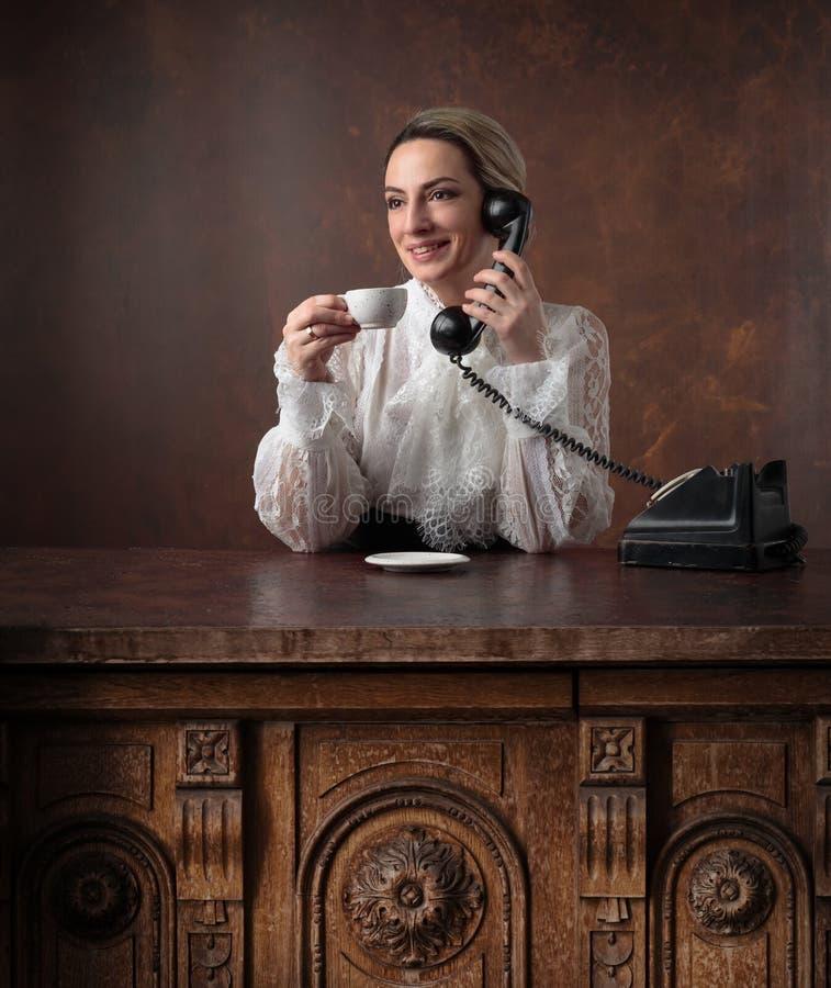 Portret van een vrouw in retro kleren met een kop van koffie en een oude zwarte telefoon royalty-vrije stock foto's