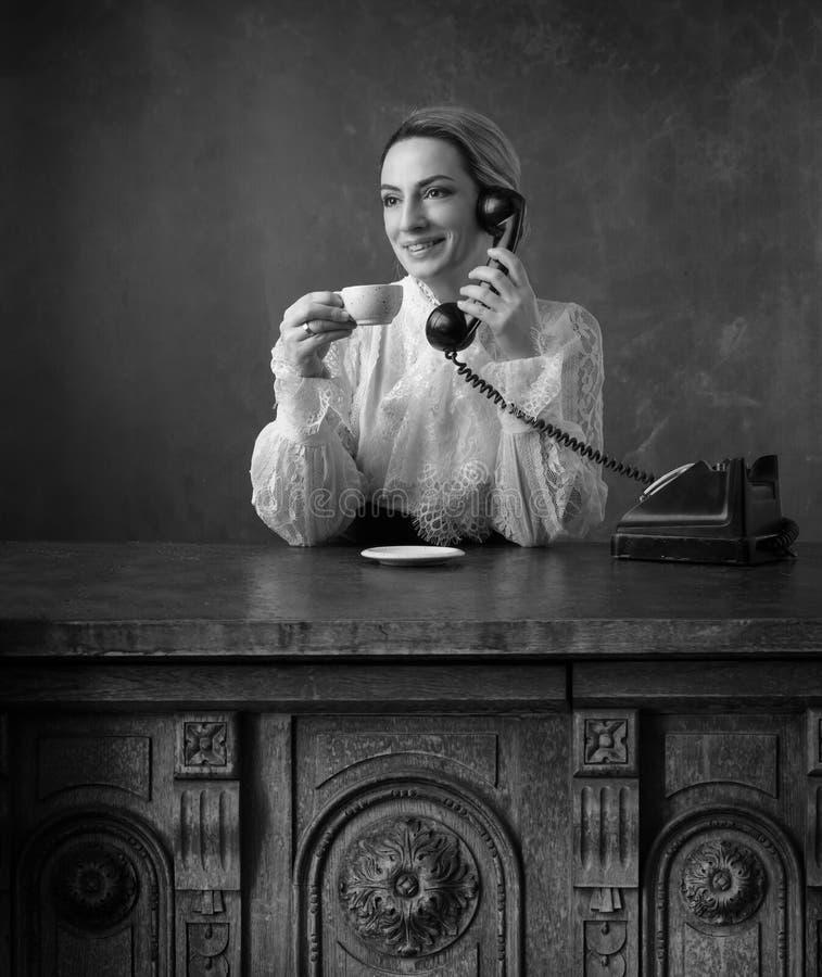 Portret van een vrouw in retro kleren met een kop van koffie en een oude zwarte telefoon stock foto's