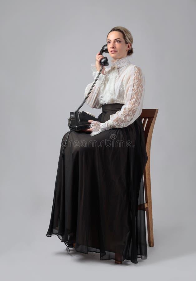 Portret van een vrouw in retro kleren met een oude zwarte telefoon stock fotografie