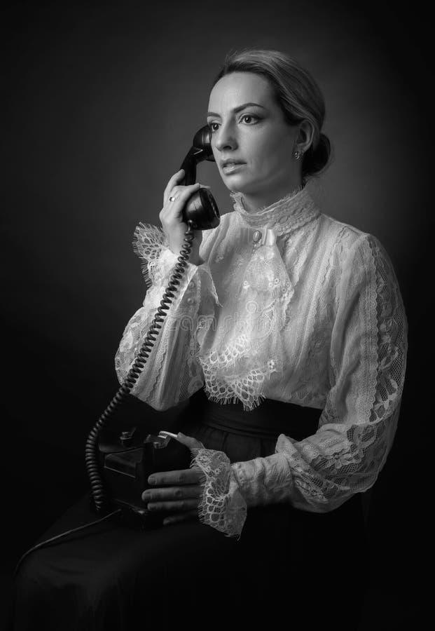 Portret van een vrouw in retro kleren met een oude zwarte telefoon royalty-vrije stock afbeeldingen