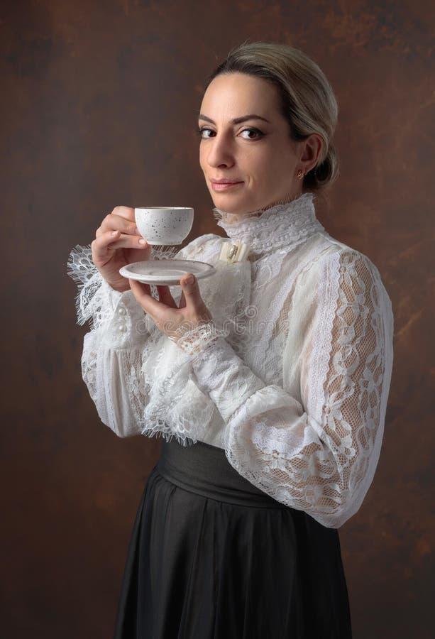 Portret van een vrouw in Victoriaanse kleren met een kop van koffie royalty-vrije stock foto