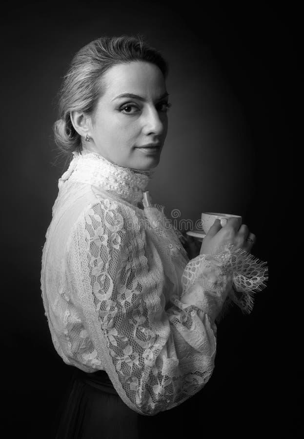 Portret van een vrouw in Victoriaanse kleren met een kop van koffie stock foto