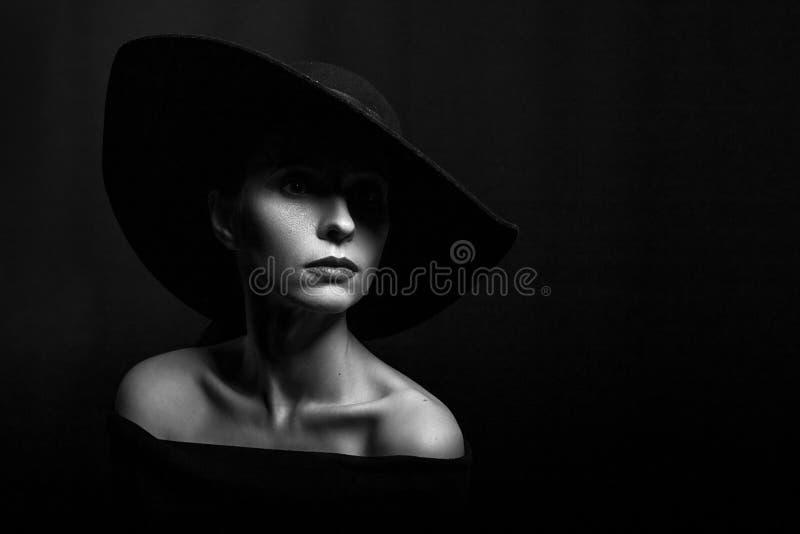 Portret van een vrouw in een zwarte hoed op een zwarte zwart-witte foto als achtergrond stock fotografie