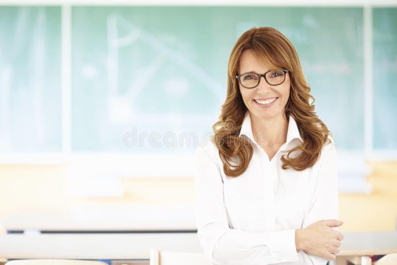 Portret van een vrouwelijke leraar met bord stock afbeelding