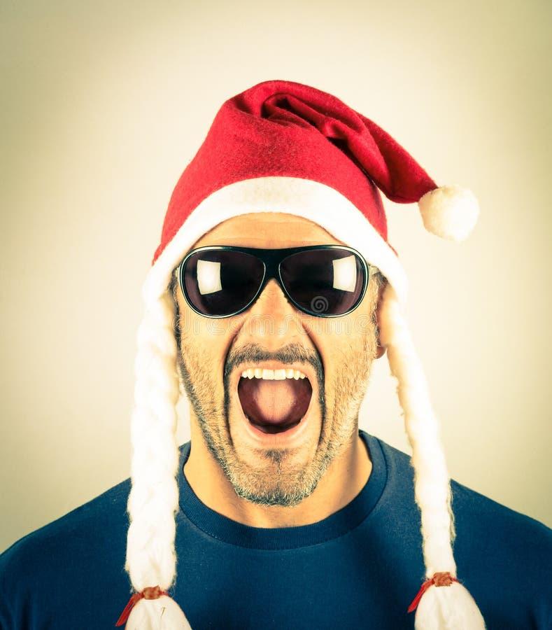 Portret van een wanhopige jonge mens met de rode hoed van Santa Claus stock afbeelding