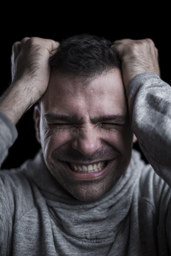 Portret van een wanhopige mens met handen op zijn hoofd Zwarte achtergrond verticaal royalty-vrije stock afbeeldingen