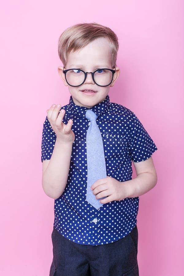Portret van een weinig glimlachende jongen in grappige glazen en band school peuter Manier Studioportret over roze achtergrond stock fotografie