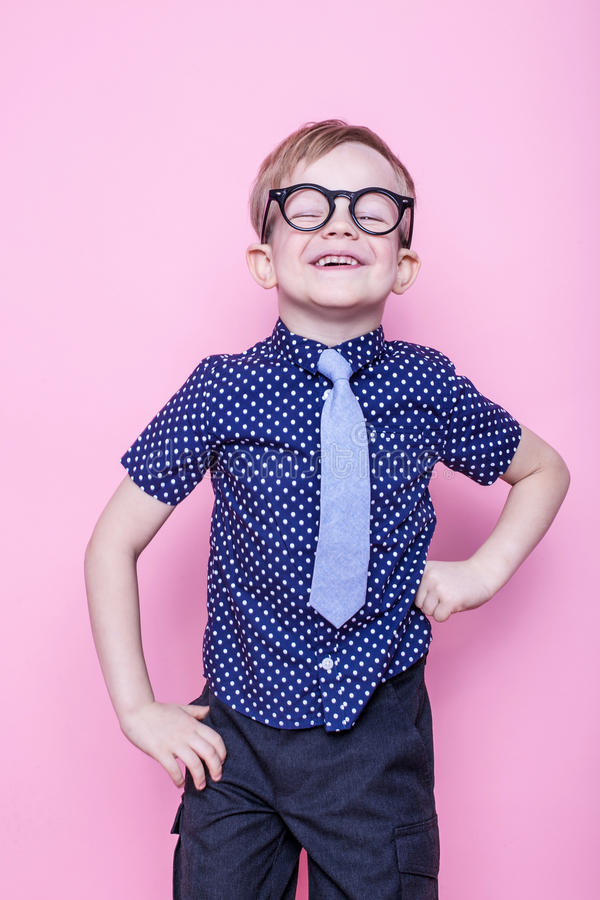 Portret van een weinig glimlachende jongen in grappige glazen en band school peuter Manier Studioportret over roze achtergrond royalty-vrije stock afbeeldingen
