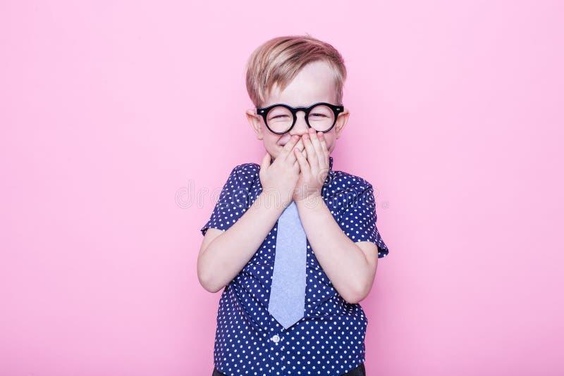 Portret van een weinig glimlachende jongen in grappige glazen en band school peuter Manier Studioportret over roze achtergrond royalty-vrije stock afbeelding