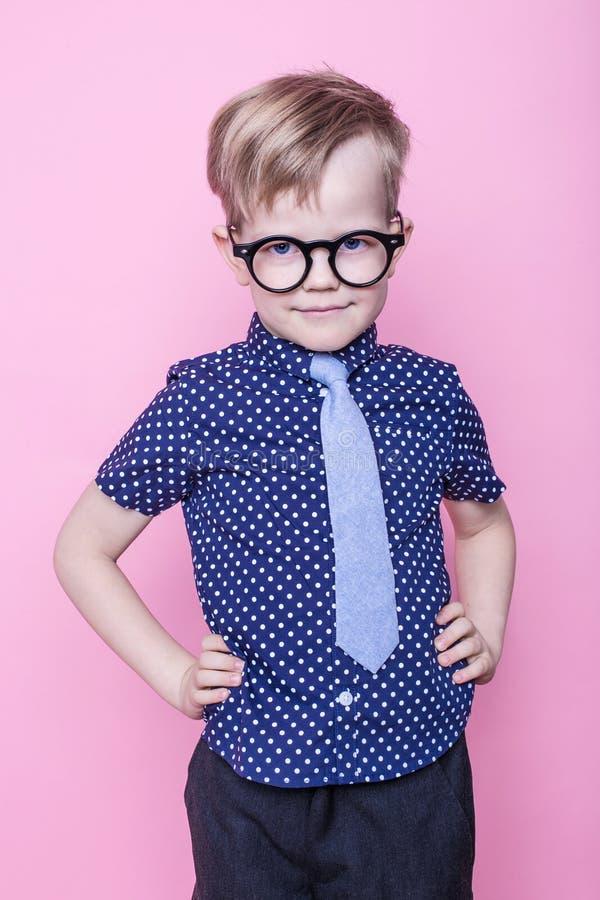 Portret van een weinig glimlachende jongen in grappige glazen en band school peuter Manier Studioportret over roze achtergrond stock foto