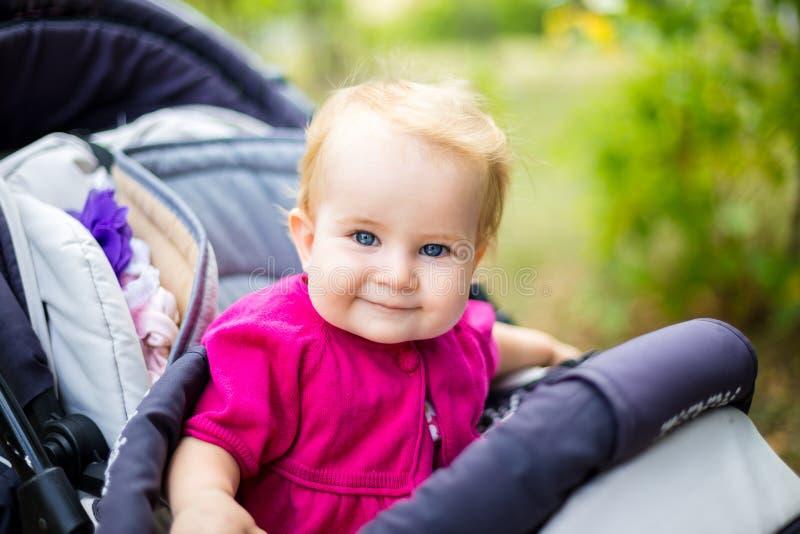 Portret van een weinig grappig kindmeisje blond met blauwe ogen die in een babywandelwagen zitten in de zomer voor greens Trinasp stock afbeeldingen