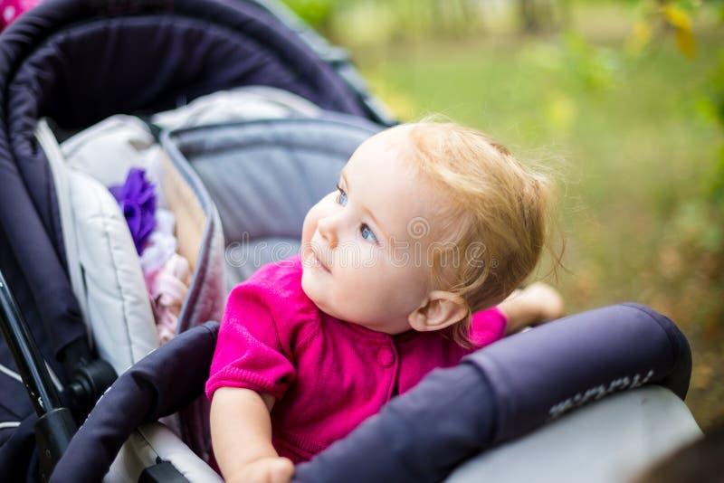 Portret van een weinig grappig kindmeisje blond met blauwe ogen die in een babywandelwagen zitten in de zomer voor greens Trinasp stock foto