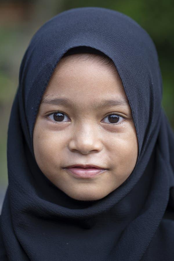 Portret van een weinig Indonesisch moslimmeisje bij de straten in Ubud, eiland Bali, Indonesië Sluit omhoog royalty-vrije stock afbeelding